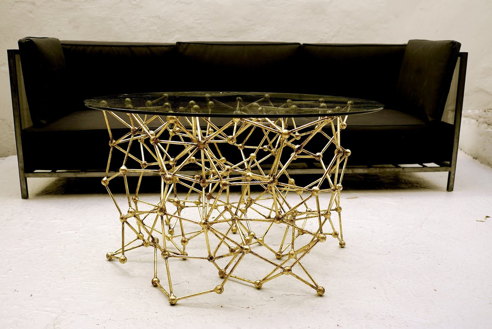 Molecular Coffee Table With Gold Leaf Finish In Front Of A Black Sofa