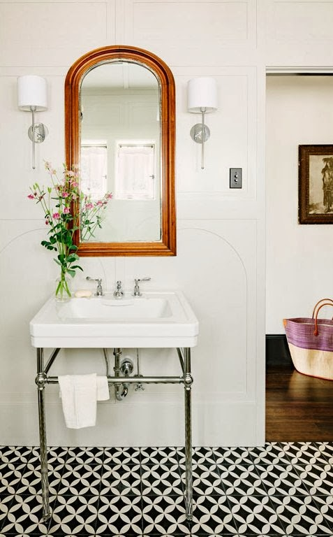 Small bathroom with black and white cement tiles, arched paneled walls and a simple wash basin sink and arched mirror