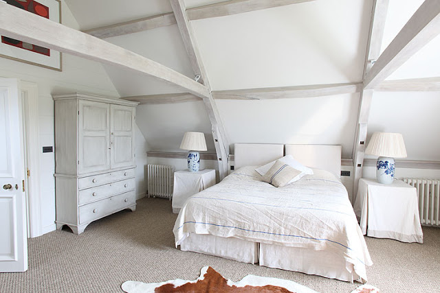 modern rustic bedroom with exposed beams, animal skin rug, carpeted floors, white wardrobe and two accent table with table cloth and matching lamps