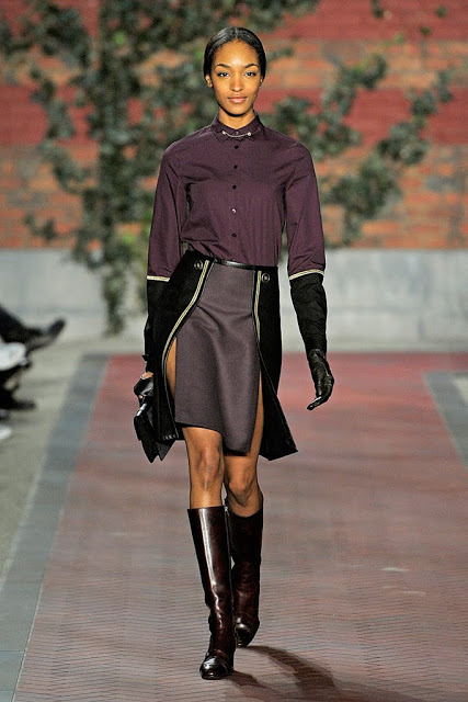 model from tommy hilfiger's fall rtw 2012 collection wearing a black, purple and gray skirt with slits and yellow piping trim and black opera gloves