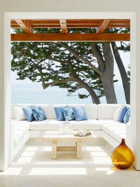 outdoor patio with white sectional sofa with blue accent pillows, light reclaimed wood coffee table and a view of the ocean