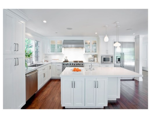 White kitchen with stainless appliances, three pendant lights and a hardwood floor