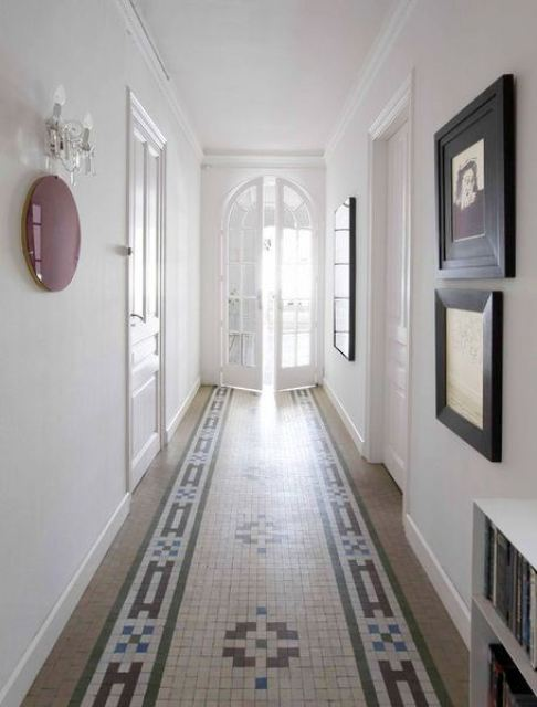 foyer in Barcelona home with mosaic tile floor, white walls with minimalist decorations and a white arched French doors