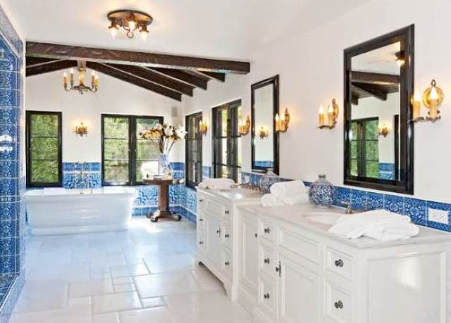 bathroom with blue and white tiles, two bathroom vanities with white drawers and cabinets below two black framed mirrors