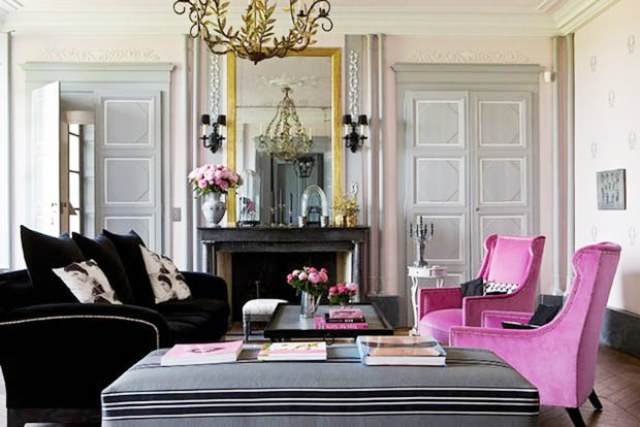 Pink and grey living room in a french mansion with black sofa, two pink wingback chairs, a marble fireplace wth a traditiona mirror, paneled doors, chandelier covered in leaves and a long grey ottoman