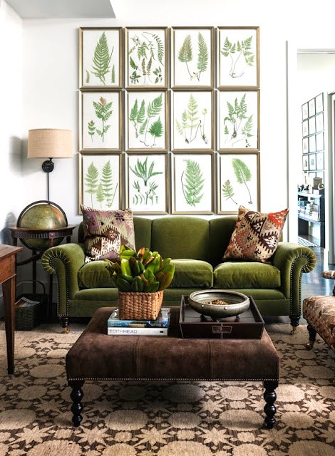 Living room with a gallery wall, green velvet sofa with nail head trim and a globe