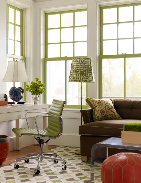 Home office with a brown sofa with chartreuse piping, a white desk with a metal rolling chair with a chartreuse seat and back, white walls, chartreuse window trimmings and an orange Moroccan pouf with chartreuse stitching and a Lucite coffee table