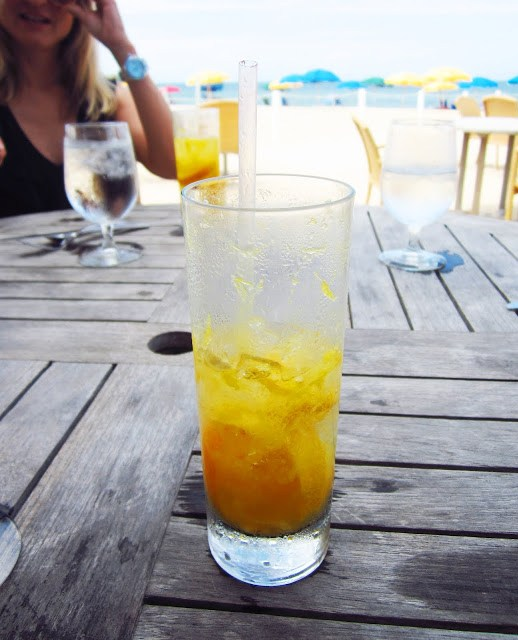 orange fizzy drink on a wood table on the beach