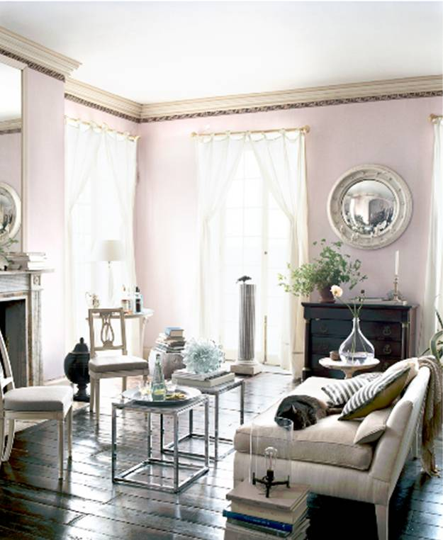 Living room with lavender walls, dark wood floor, mercury side tables, a white sofa, breeze white curtains and a round mirrors hanging above a dark wood chest of drawers