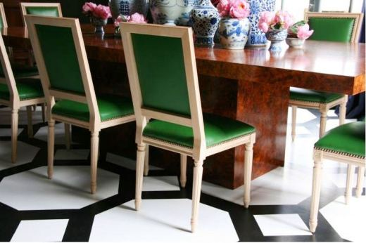 Close up of the green upholstered chairs and their nailhead trim and the black and white painted floor in a dark living room