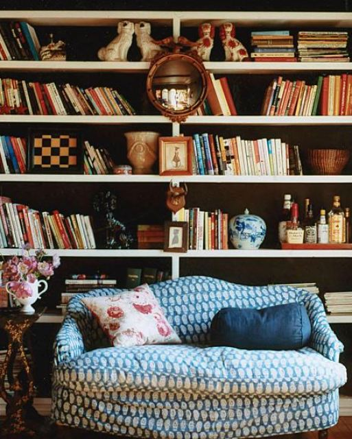 melanie acevedo's library with blue loveseat sofa with a built in bookshelf full of books