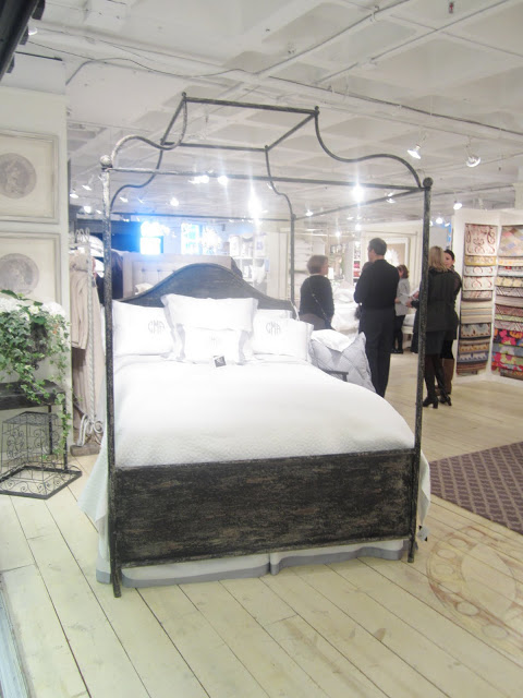 Large bed with metal canopy frame by Corsican at the The center room at Christian Mosso Associates showroom