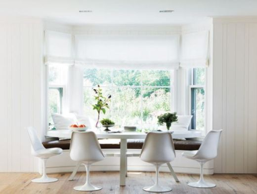 White breakfast nook with saarninen chairs and banquette leather window seating