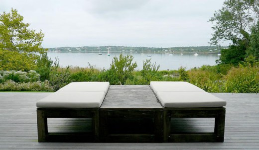 Modern lounge chairs on an outdoor patio overlooking a lake in Montauk on Long Island
