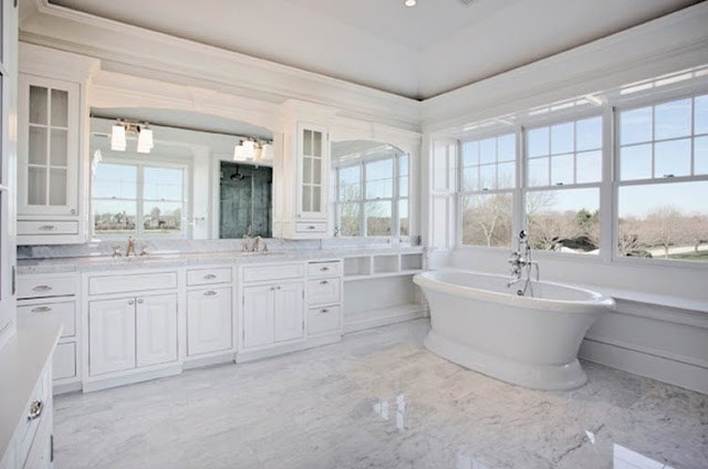 large white master bathroom with lots of widows, white cabinets and a stand alone tub