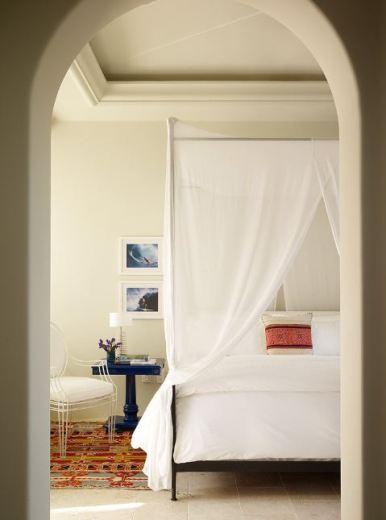 Simple and elegant bedroom with arched door way, white canopy, lucite Casamidy Louis XIV chair, blue nightstand and a patterned rug