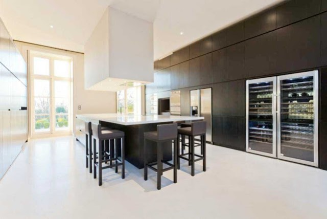modern kitchen with hidden appliances, black island with white counter top, over sized square pendant light, bar chairs, and two wine cabinets