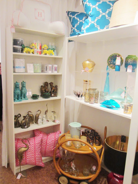 COCOCOZY Pillows in pink and peacock blue on a white shelf surrounded by other vintage finds
