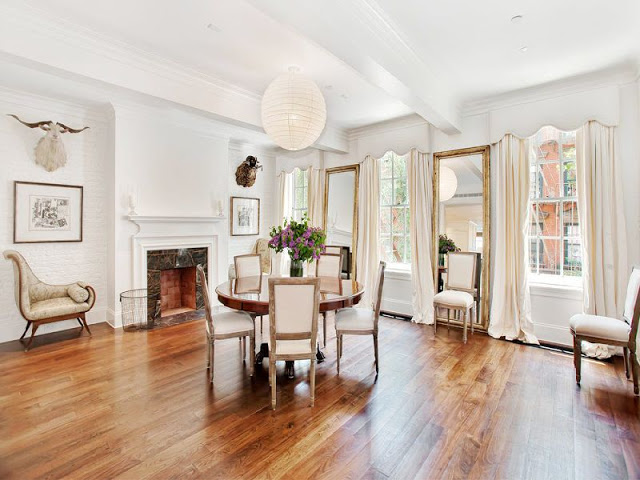 grand dining room with wood floors, a marble fireplace, a small round wooden table and two large decorative mirrors.
