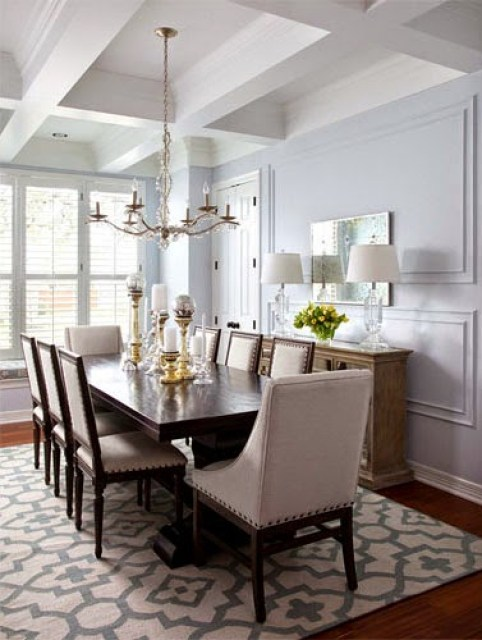 Dining room with mismatched chairs and a graphic print rug