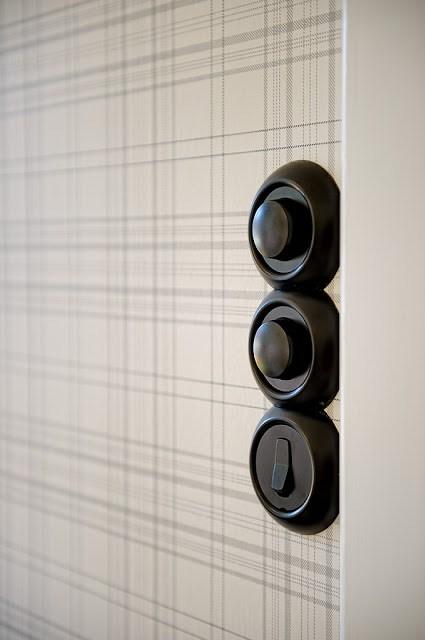 plaid wallpaper with dark brass light switches