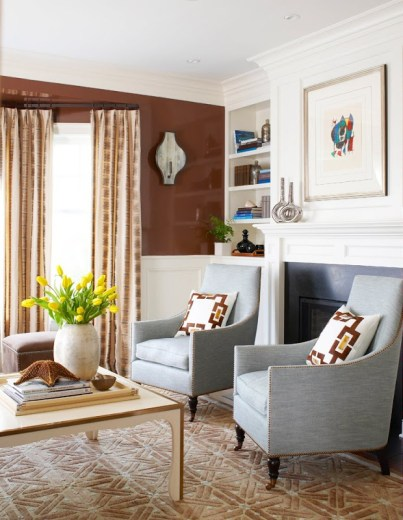 Alternative view of the living room with two grey armchairs, a fireplace, built in book cases and a white accent table with a starfish