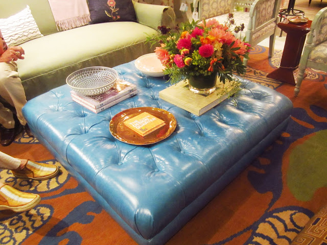 turquoise leather square ottoman being used as a coffeetable