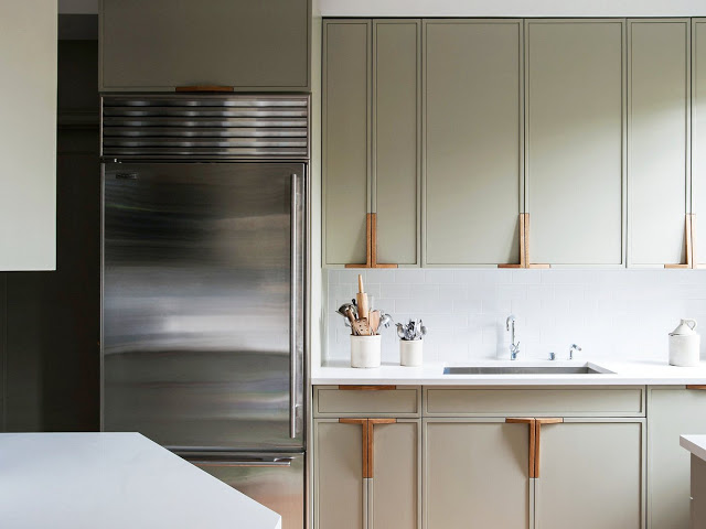 Close up of the greige cabinets and their L shaped wood door handles in the kitchen