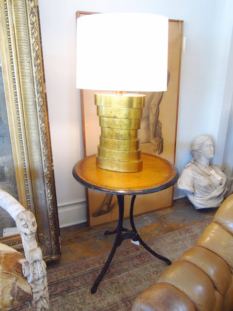 Table lamp with brass base on a round wooden side table