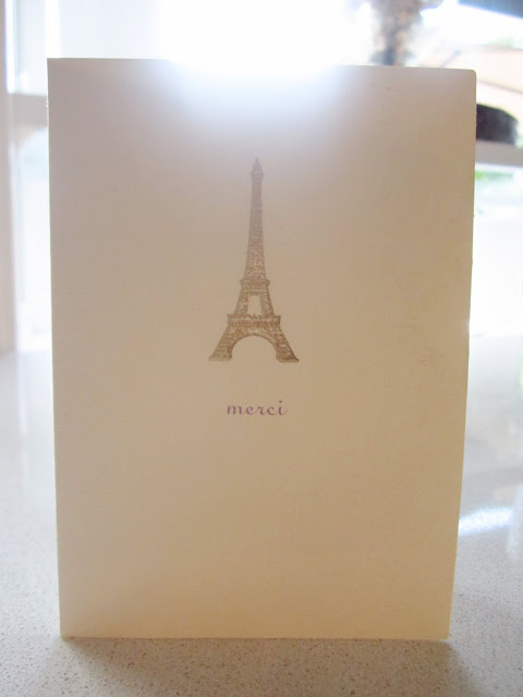 """Cream colored card with the  Eiffel Tower and """"Merci"""" written below it"""