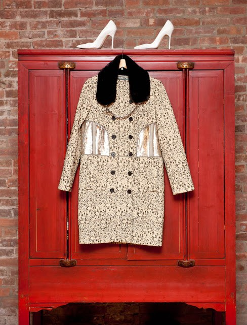 Red wardrobe in front of a brick wall with a pair of white heels on top and a jacket with fur trim hanging on the front