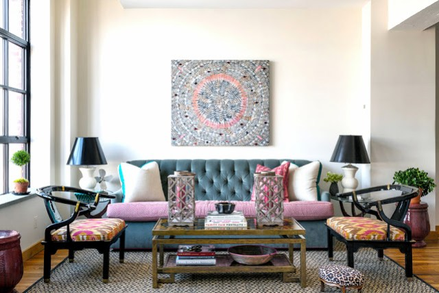 Anne Maxwell's colorful NYC loft apartment's living room with a gray Kravet Medley sofa, armchairs, two side tables with matching ceramic lamps and an Oscar de la Renta coffee table