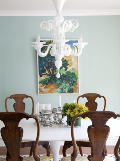 Opaque white Murano glass chandelier in a dining room with wood chairs around a white table and mint walls