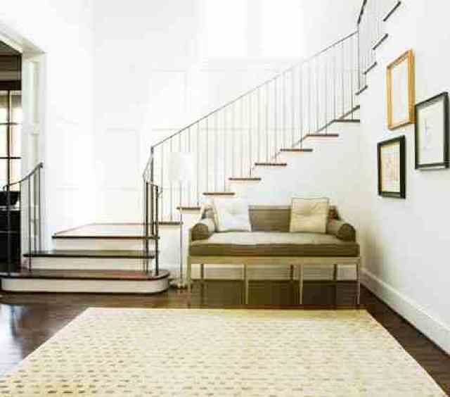 Foyer with Louis XVI bench, staircase, area rug and dark wood floor