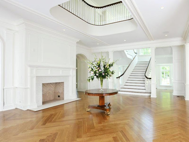 foyer with white grand staircase, fire place and herringbone wood floor