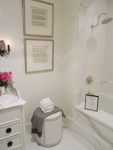 Bathroom in the House of Windsor with white beadboard paneled walls, carrara marble bath with an arch, a little leather stool with nail head trim, white cabinets, pink peonies and a wall mounted candlestick inspired light