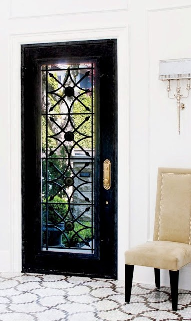 glossy black front door, marble mosaic tiles and a high back neutral chair with dark legs