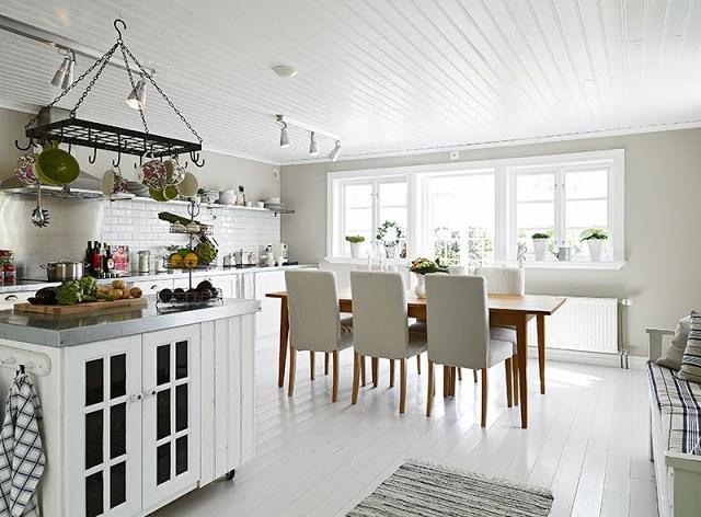White kitchen swedish cottage wood table high back chairs painted wood floor white subway tile backsplash