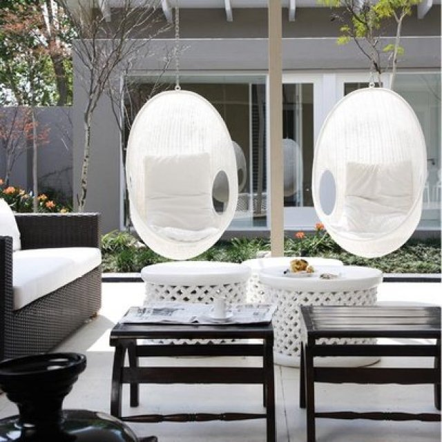White hanging chairs in a family room with glass walls and dark wicker sofa with white cushions, two dark wood side tables and round white footrests with woven detailing on the side