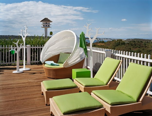 Outdoor patio with wicker lounge chairs with green cushions by Ghislaine Vinas