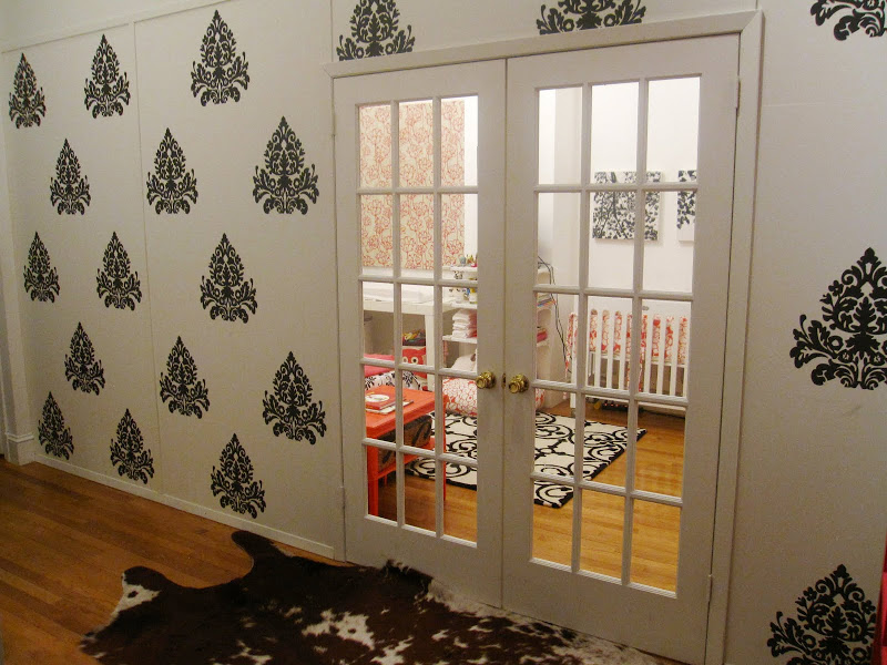 Entry way outside a nursery with dark grey medallion brocade wall decals, French doors and a cowhide rug