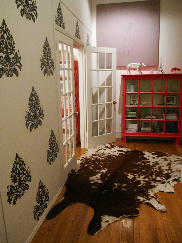 Entry way outside a nursery with dark grey medallion brocade wall decals, a hot pink glass cabinet, and a cowhide rug