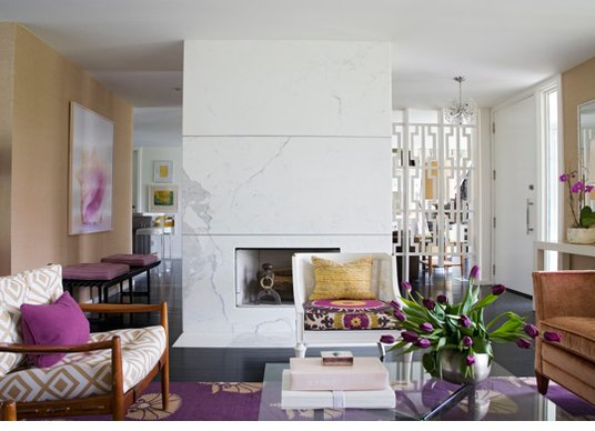 Modern living room with white marble fireplace and purple rugs, accent pillows, flowers and art