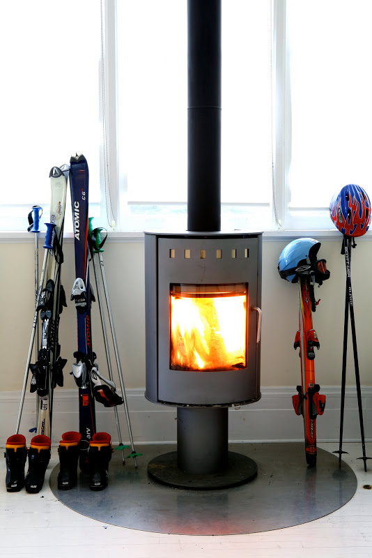 Freestanding fireplace in a living room by Robert and Cortney Novogratz surrounded by ski gear