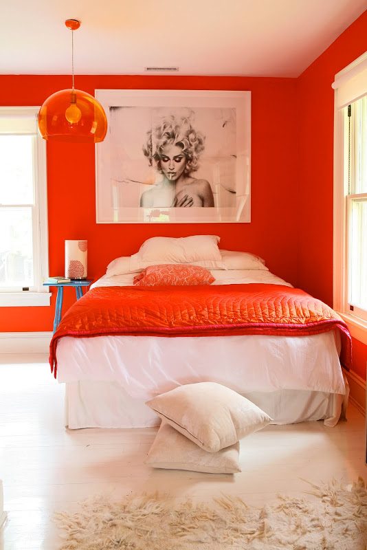 Bright orange walls in a bedroom by Robert and Cortney Novogratz with matching pendant light