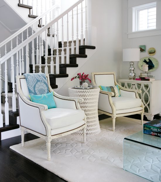 Modern meets traditional in a light airy living room with white Louis XIV armchairs and a white woven sidetable