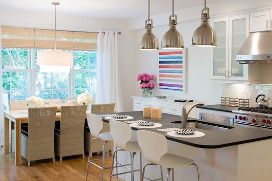 Open plan kitchen and dining room by Lynn Morgan with metal pendant lights, black countertops and stainless appliances in the kitchen and a farmhouse style table and high back wicker chairs in the dining room