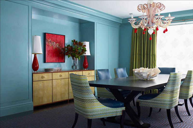 Blue dining room with a white and red glass chandelier, green curtains, and multicolored Missoni-esque upholstered dining chairs
