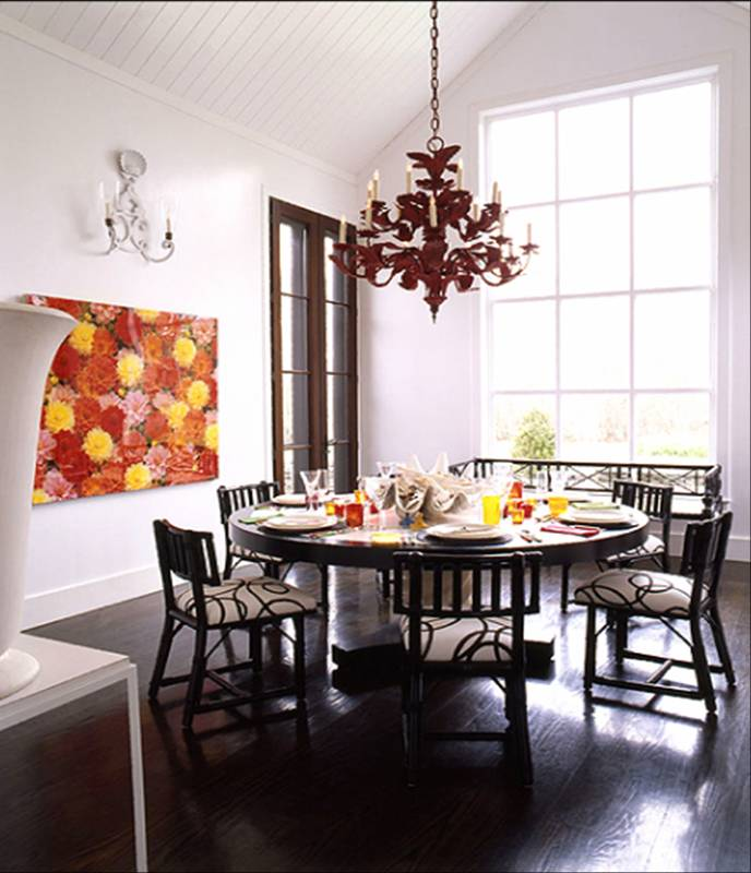 Dark dining room with iron tole red chandelier, large round table, dining chairs upholstered in black and white print and a bold and colorful floral painting