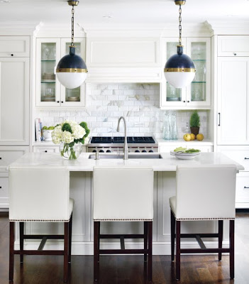 White kitchen with marble subway tile backsplash, cabinets topped with crown molding, a custom panel to cover range hood, nailhead trim counter stools and Thomas O'Brien antique brass, blue and white glass banded Hicks pendant lights